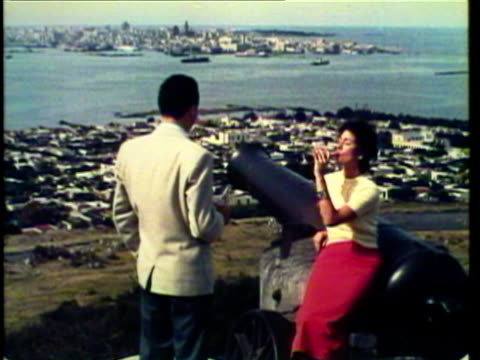 1953 ms couple sitting on canon drinking coke / montevideo, uruguay / audio  - モンテビデオ点の映像素材/bロール