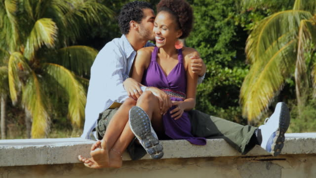 WS Couple sitting on cement hedge, hugging and kissing / Havana, Cuba