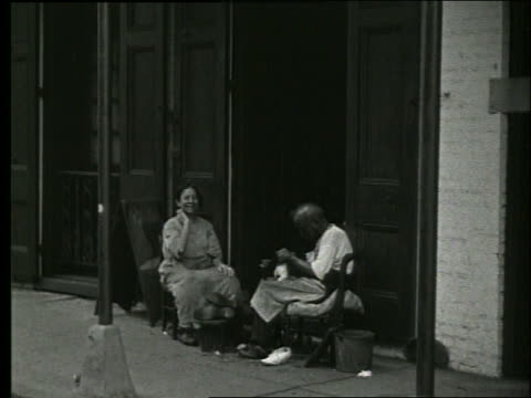 vidéos et rushes de b/w couple sitting on chairs on sidewalk in front of bldg / 1915 new orleans / no sound - 1910