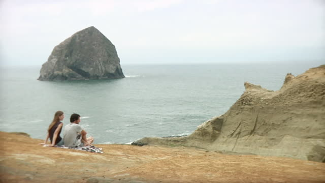ws pan couple sitting on cliff with sea in background / cape kiwanda, oregon, usa - legs crossed at ankle stock videos & royalty-free footage