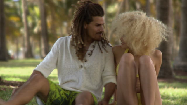 ms couple sitting on grass, leaning at each other and laughing / south beach, florida, usa - shorts stock-videos und b-roll-filmmaterial