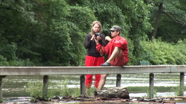 couple sitting on guard rail of parkway shooting photos. zoom back to reveal area. bronx river parkway flooded on august 28, 2011 in scarsdale, new... - hurricane irene stock videos & royalty-free footage