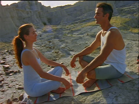 profile couple sitting on mat + meditating by buttes / southwestern us - lotussitz stock-videos und b-roll-filmmaterial
