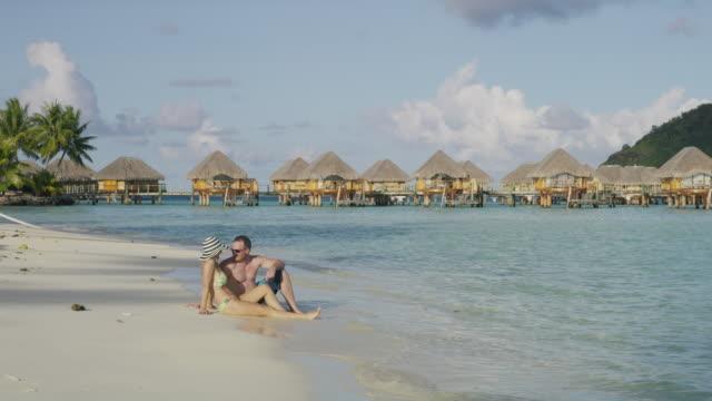 couple sitting on ocean beach near bungalows in tahiti / bora bora, french polynesia - tahiti stock videos and b-roll footage