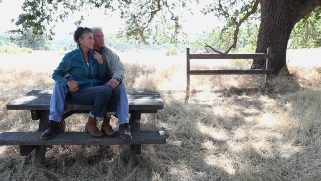 Couple sitting on picnic table and walking away
