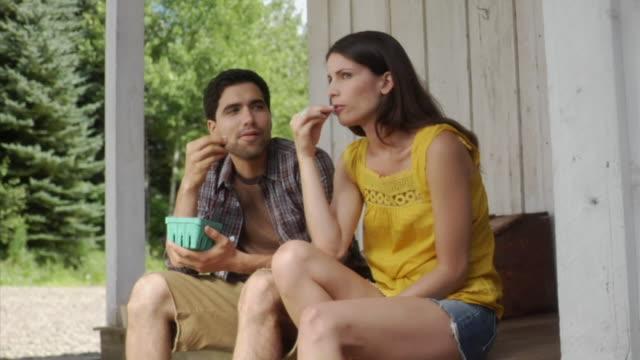 stockvideo's en b-roll-footage met ms couple sitting on porch eating berries, bovina center, new york, usa - driekwartlengte