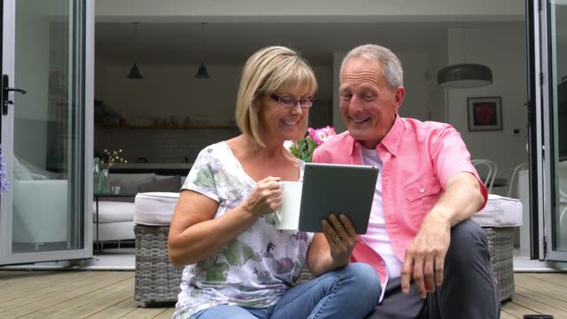 Couple sitting on porch looking at something on tablet