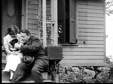 vidéos et rushes de 1915 b/w ms couple sitting on porch, then woman's angry father arrives, sends man away, and sends her inside - fille de