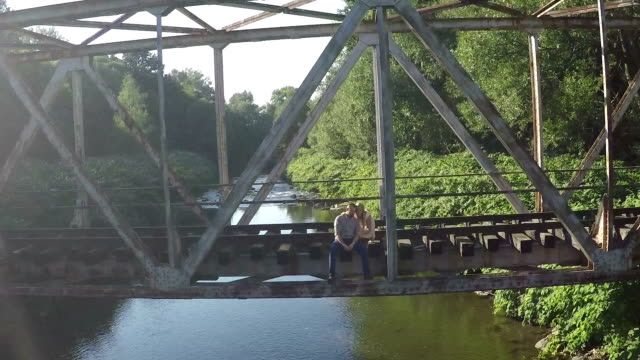 AERIAL ZOOM OUT Couple sitting on railroad bridge on sunny day