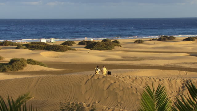 vidéos et rushes de ws zi couple sitting on sand dune on beach near sea / maspalomas, gran canaria, spain - couple d'âge mûr