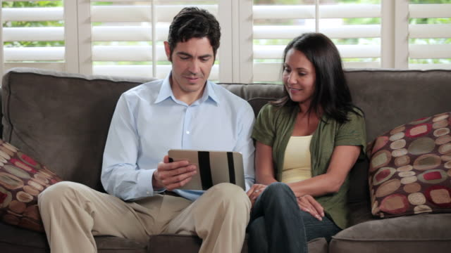 ms couple sitting on sofa and browsing on tablet computer / portland, oregon, united states - choosing stock videos and b-roll footage