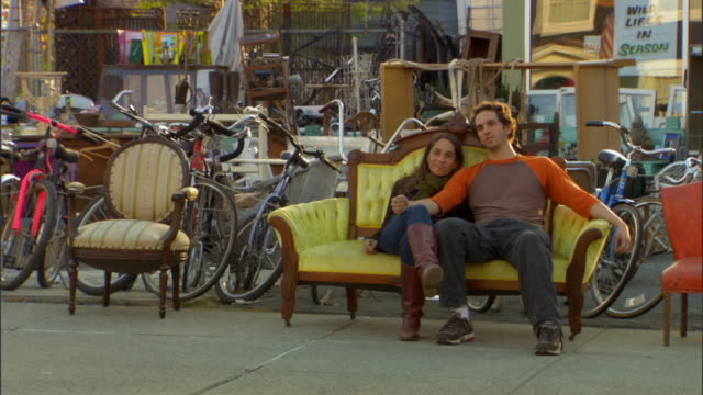 vídeos de stock, filmes e b-roll de ws couple sitting on sofa at outdoor antique market/ livingston, new york - antiquário loja