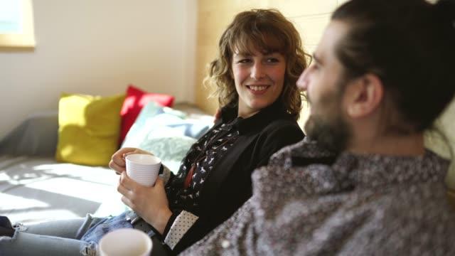 ehepaar sitzt auf sofa und trinkt tee - ehefrau stock-videos und b-roll-filmmaterial