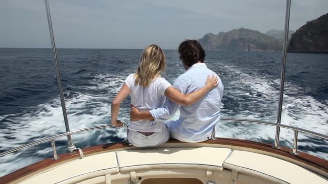 ms pov couple sitting on stern of motorboat / port de soller, mallorca, baleares, spain - barca da diporto video stock e b–roll