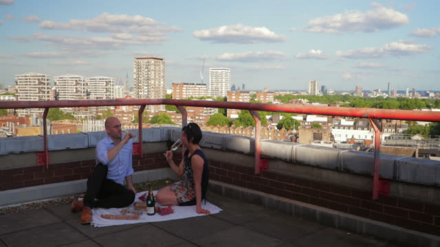 couple sitting on the rooftop of building enjoying a picnic - picnic stock videos and b-roll footage