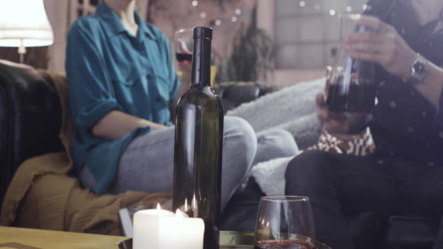 Couple Sitting On The Sofa Drinking Wine Catching Up At Home
