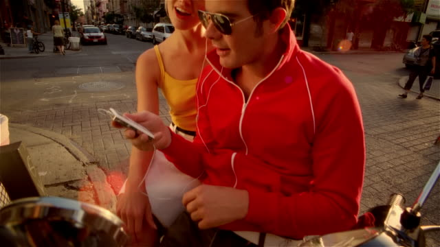 Couple sitting on Vespa on street listening to MP3 player