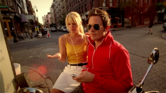 Couple sitting on Vespa, singing and dancing along to music on MP3 player, and kissing