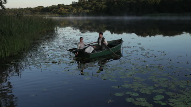 couple sitting still in rowing boat as water ripples around the boat. - xix secolo video stock e b–roll
