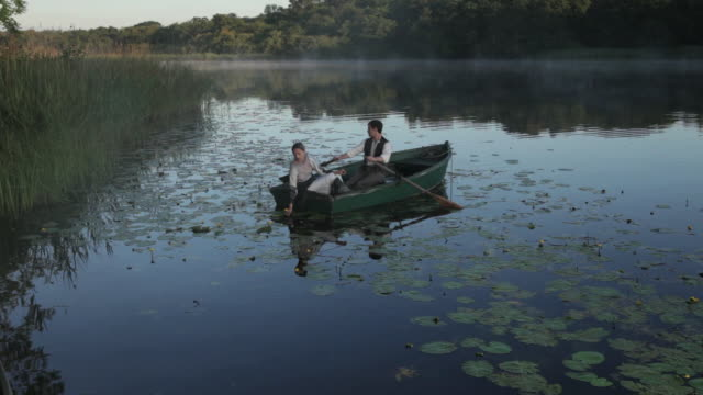 Couple sitting still in rowing boat as water ripples around the boat.