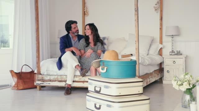 stockvideo's en b-roll-footage met couple sitting - dubbel bed
