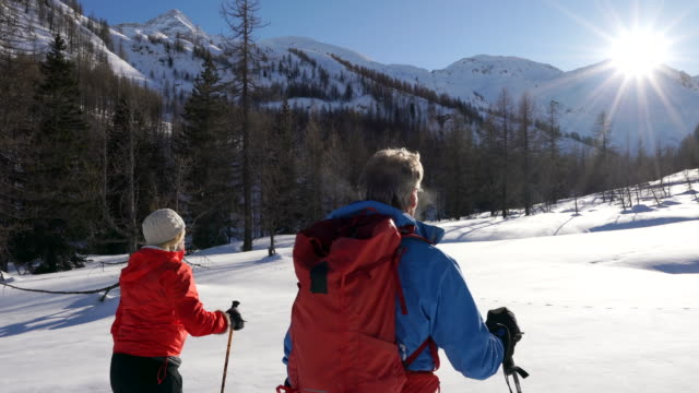 stockvideo's en b-roll-footage met couple ski tour up snowy valley at sunrise - ski jack