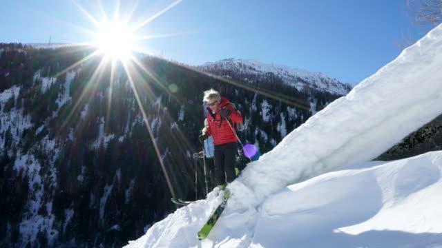 paar ski touring verschneiten grat - teil einer serie stock-videos und b-roll-filmmaterial