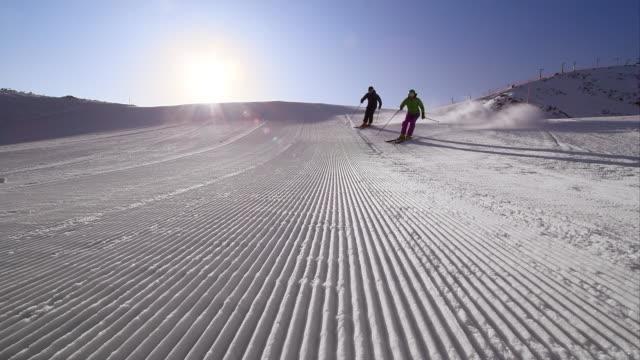 vídeos de stock e filmes b-roll de slo mo ds couple skiing down groomed run in morning - bastão de esqui