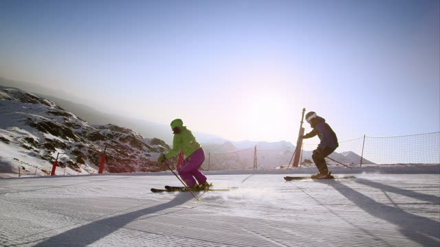 slo mo ts couple skiing down slope in morning sun - moving down stock videos & royalty-free footage