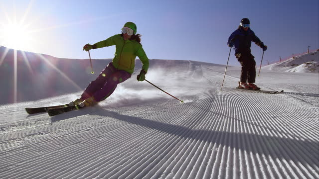 vídeos de stock e filmes b-roll de slo mo ds couple skiing down the groomed slope - bastão de esqui
