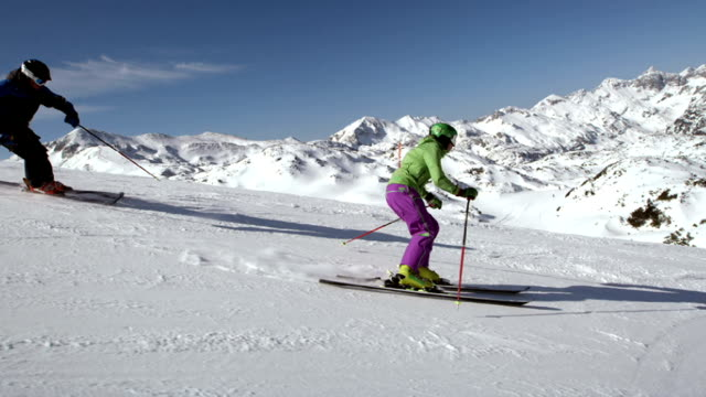 slo mo couple skiing down the slope on sunny day - skiing stock videos & royalty-free footage