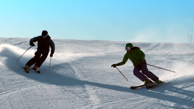 slo mo couple skiing down the slope - skiing and snowboarding stock videos and b-roll footage