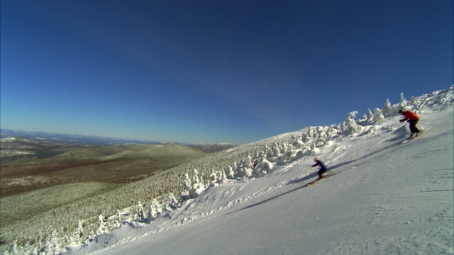 ws pan couple skiing down traditional snow-laden new england ski slope / rangeley, maine, usa - bastoncino da sci video stock e b–roll