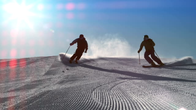 slo mo ld couple skiing on a sunny day - winter sport stock videos and b-roll footage