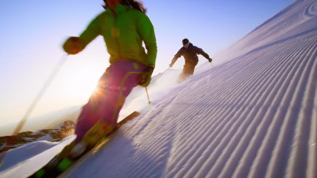 vídeos de stock e filmes b-roll de slo mo couple skiing the groomed slope in early morning - bastão de esqui