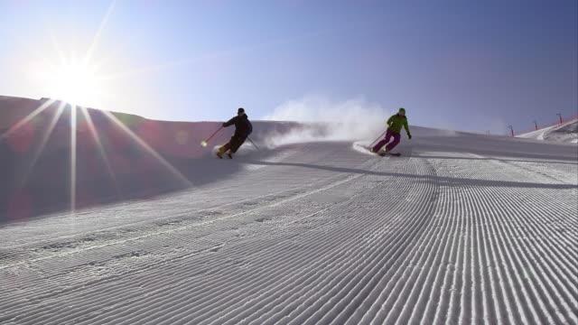 vídeos de stock e filmes b-roll de slo mo ds couple skiing the groomed sunny track - bastão de esqui