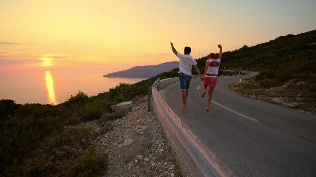 couple skipping down the coastal road at sunset - skipping stock videos & royalty-free footage