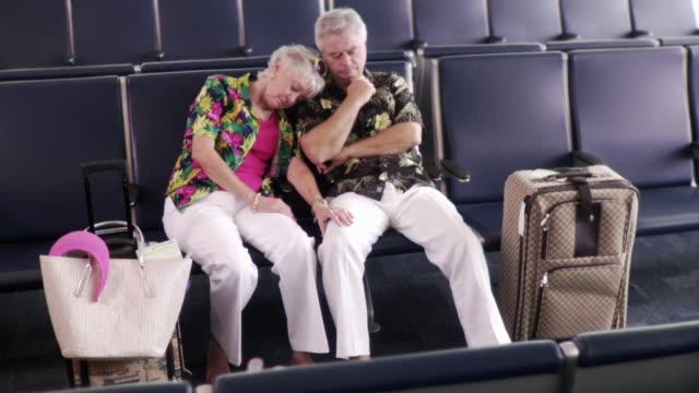 WS PAN Couple sleeping in airport departure lounge / Jacksonville, Florida, USA