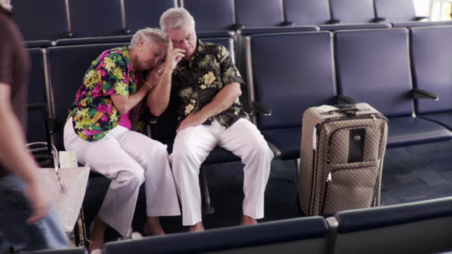 WS Couple sleeping in airport departure lounge / Jacksonville, Florida, USA