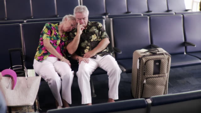 ws couple sleeping in airport departure lounge, thief walks up goes through suitcase and steals item / jacksonville, florida, usa   - thief stock videos & royalty-free footage