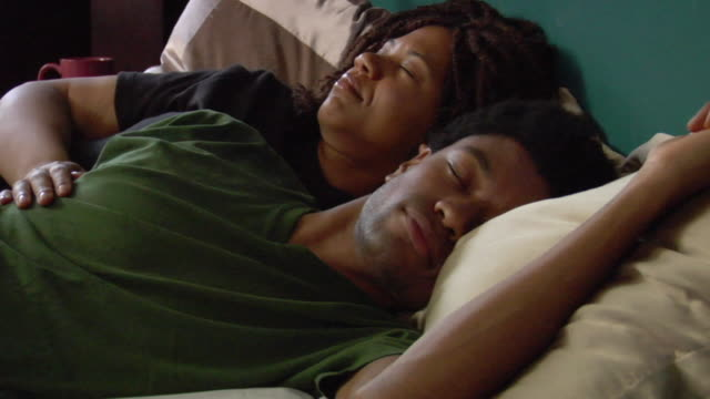 MS Couple sleeping in bed/ Man waking to alarm clock and turning it off/ New York City