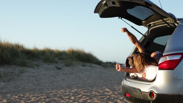 MS couple sleeping in car on beach open back hatch in the morning/Tarifa/Andalucia/Spain