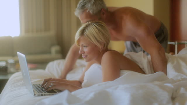 ms couple sleeping on bed working on laptop / seattle, wa, united states - shoulder stock videos and b-roll footage