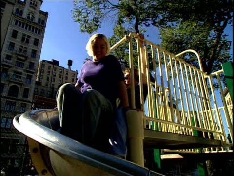 couple sliding down slide at nyc playground - 屋外遊具点の映像素材/bロール