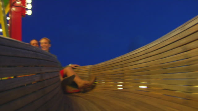 ws rear pov couple sliding down wooden slide, oktoberfest, munich, germany - rutschen stock-videos und b-roll-filmmaterial