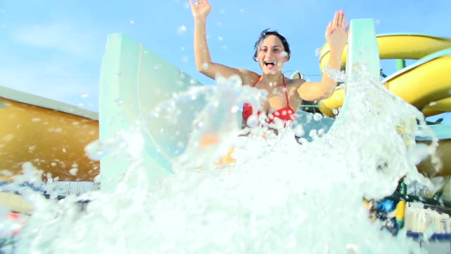 hd super slow-mo: couple sliding on water slide - water slide stock videos & royalty-free footage