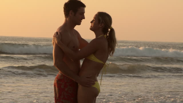 vidéos et rushes de couple slow dances and kisses at waters edge during sunset at the beach - slow