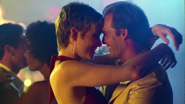 ms couple slow dancing, talking, kissing + smiling on dance floor in nightclub - 恋に落ちる点の映像素材/bロール