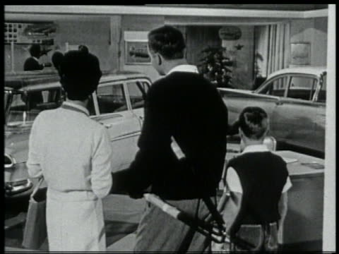 b/w 1959 rear view couple + small boy looking at cars in chevy showroom - 1950 1959 stock videos and b-roll footage