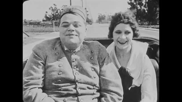 vidéos et rushes de 1918 couple (fatty arbuckle and alice lake) smile as they ride in a horse carriage - 1918
